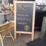 Foto van een bord bij De Waag waarop staat dat betalen met Bitcoin mogelijk is.