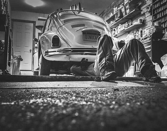 Zwart-wit foto van een automonteur die bezig is met een Volkswagen Kever. Zoals we bij Mackrad.nl graag WordPress websites onderhouden.