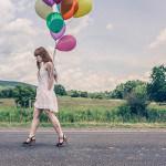 Foto van een vrouw die met ballonnen over straat loopt.
