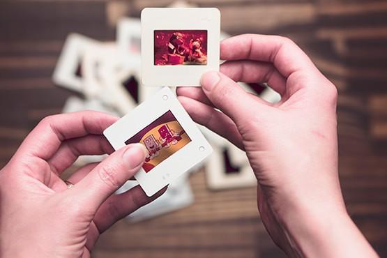 Foto van twee handen die twee dia's vasthouden en die wij gebruiken om een backup uit te beelden.