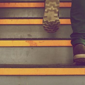 Foto van de voeten van iemand die een trap op loopt.