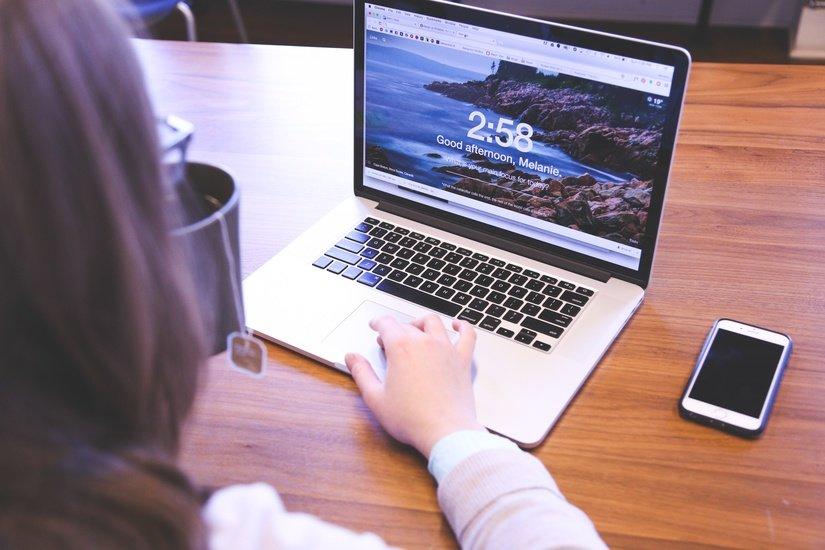 Foto van een vrouw die bezig is op haar laptop.