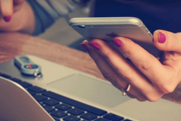 Rechtenvrije foto via Unsplash van een vrouw die een responsive website bezoekt op haar mobiele telefoon.