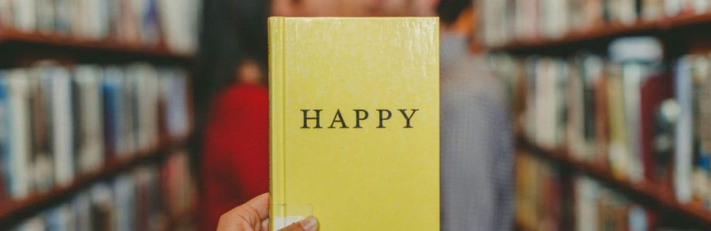 Rechtenvrije foto van Josh Felise via Unsplash van het boek Happy in een bibliotheek.