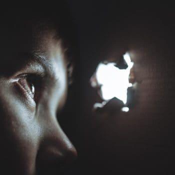 Rechtenvrije foto van spiekende jongen van Dmitry Ratushny via Unsplash.com. Voor bij artikel over Facebook tijdlijn en taggen.