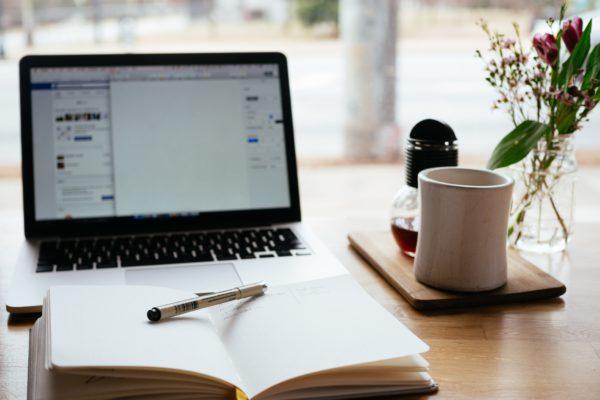 Rechtenvrije afbeelding van een laptop en een schrift door Nick Morrison via Unsplash. Minimale eisen van een website.