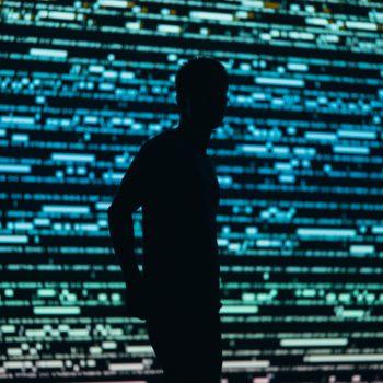 Rechtenvrijefoto van persoon voor verlichte muur door Chris Yang via Unsplash.